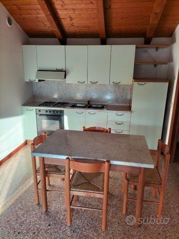 Cucina con elettrodomestici e divano