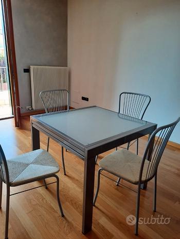 Tavolo in acciaio e vetro con sedie